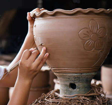 clay craft: hands of Thai style pottery working on ceramic vase Stock Photo