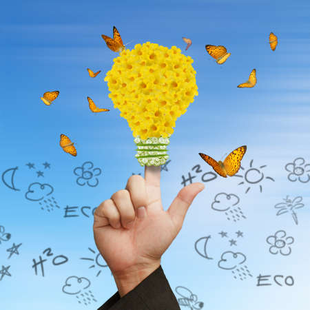 Business Hand powering light bulb as flower,butterflies, can be used for energy concept photo