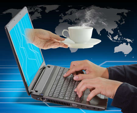 correspond: Female Hand reaches a cup of coffee out of the laptop to business man work Stock Photo