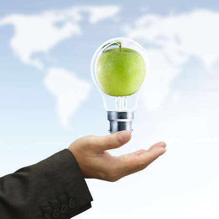 Businessman hand hold light bulb and green apple as symbol on world map background photo