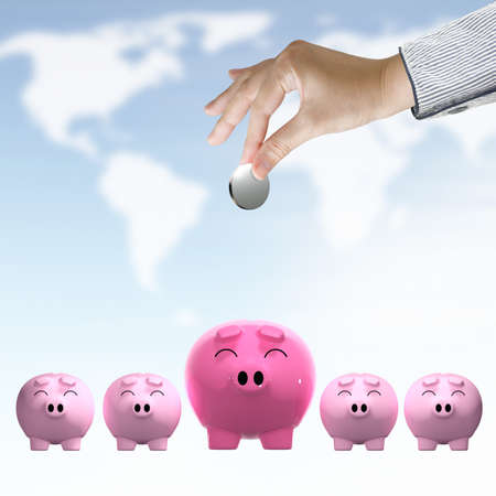 Saving,Female hand putting a coin into piggy bank on world map sky background Stock Photo - 10530695