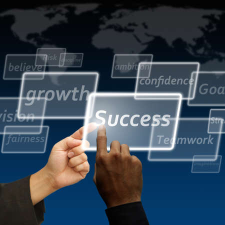 key to success: Business team touch on success virtual button on the world background Stock Photo