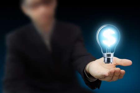 bright future: Businessman hand hold a light bulb as dollar sign as idea
