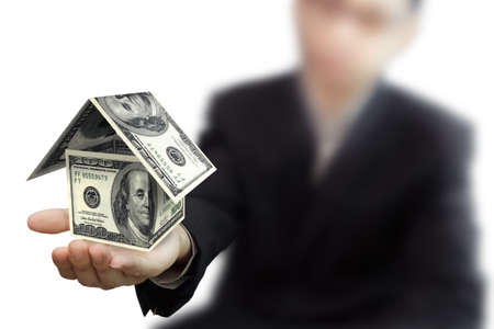 dividends: Businessman hand holds a dollar house on white background Stock Photo