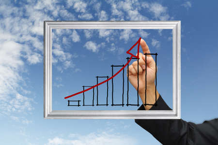safe investment: business hand point graph on screen and silver frame Stock Photo