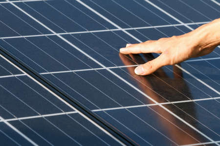 human hand touch solar panels photo