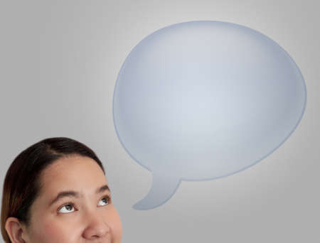 young business woman thinking in blue blank speech bubble on grey background. photo
