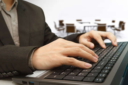 businessman hands typing on a laptop with meeting room background photo