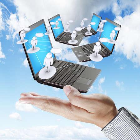 red informatica: mano sostiene port�tiles como el concepto de red social Foto de archivo