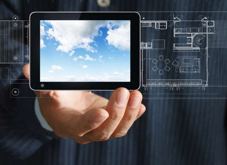 business hand holding a tablet touch screen computer on interior layout background photo