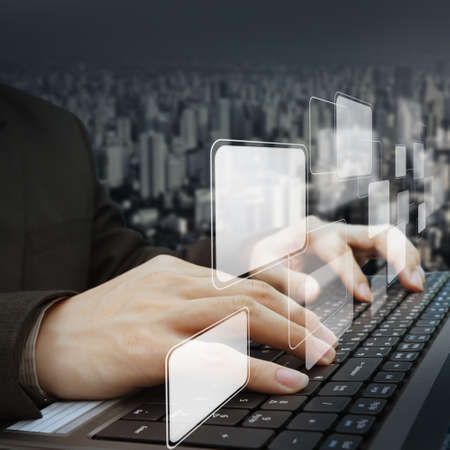 concept images: close up of businessman working with laptop and virtual buttons and city background