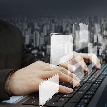 concept images: Primo piano di imprenditore che lavora con il computer portatile e pulsanti virtuali e lo sfondo della citt� Archivio Fotografico