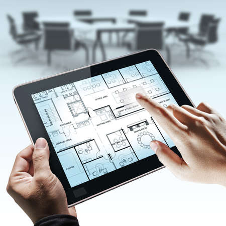 business hand point on interior layout plan on tablet computer as meeting concept photo