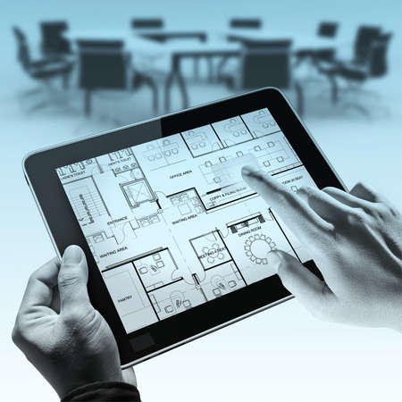 business hands point on interior layout plan on tablet computer as meeting concept photo