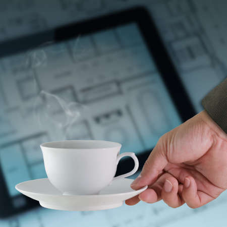 hand with a cup of coffee on tablet and blueprint background photo