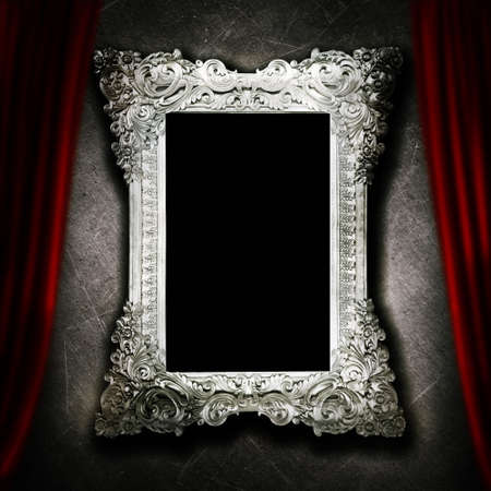 Gallery display - vintage silver frames on an old cement wall and red curtain photo