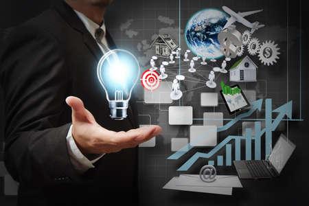 công nghệ: tay doanh nhân nắm giữ bóng đèn và bộ sưu tập kinh doanh