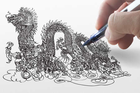 hand draws dragon on paper photo