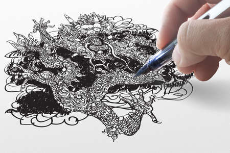 hand draws dragon on paper photo