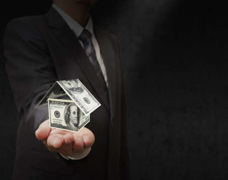 Businessman hand holds a dollar house Stock Photo - 11844103