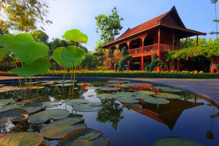 country house style: Thai style house reflected in lotus pond,Thailand Stock Photo