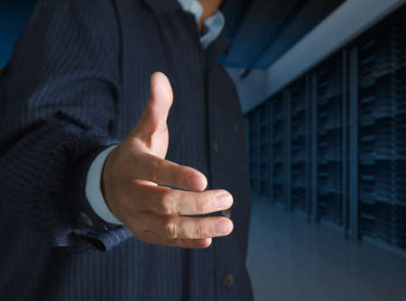 close up businessmen offer hand shake in a technology data center Stock Photo - 12602235