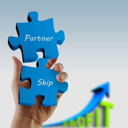 partnership  written puzzle pieces in hand Stock Photo