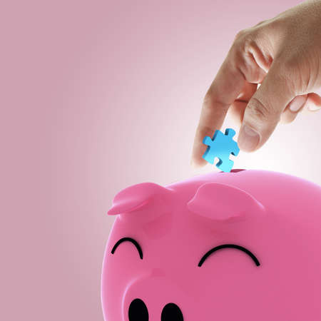 disarray: hand picking puzzle to piggy bank as concept Stock Photo