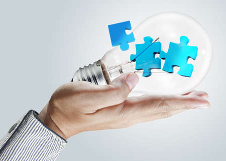 puzzle in bulb on male hand as concept Stock Photo - 12910032