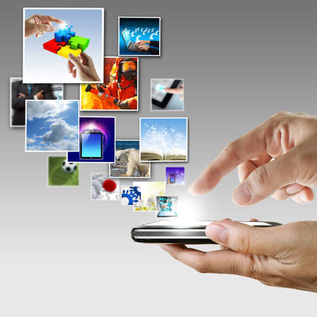 ringtones: hand holds touch screen mobile phone streaming images Stock Photo