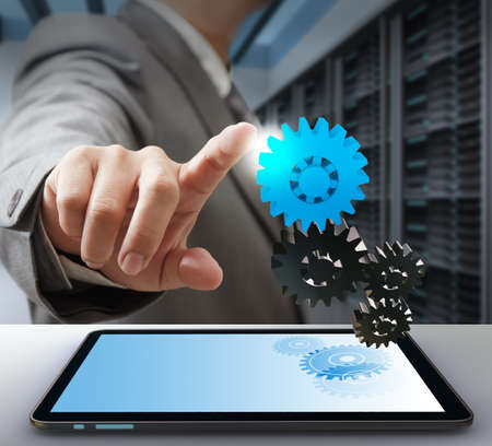 creative industries: business man touch on gear as computer solution concept Stock Photo