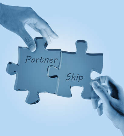 group solution: businessman and woman holding puzzle pieces with the word PARTNERSHIP written on it.  Stock Photo