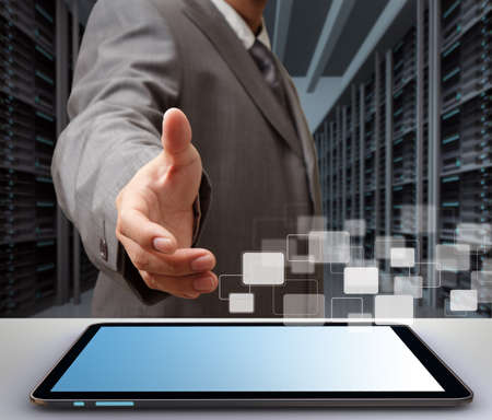 telecommunication: business man offers hand shake in a technology data center