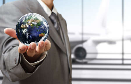 business man holds globe in the airport Elements of this image furnished by NASA  photo