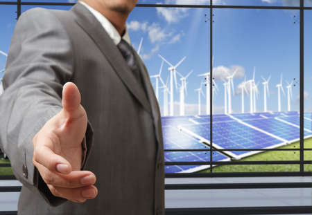 technology deal: business man offers hand shake with energy saving