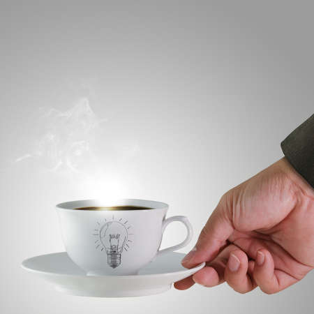 serve: hand and a cup of coffee with light bulb drawing as concept Stock Photo