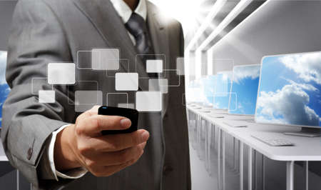 business man holds touch screen mobile phone in computer room Stock Photo - 13310181
