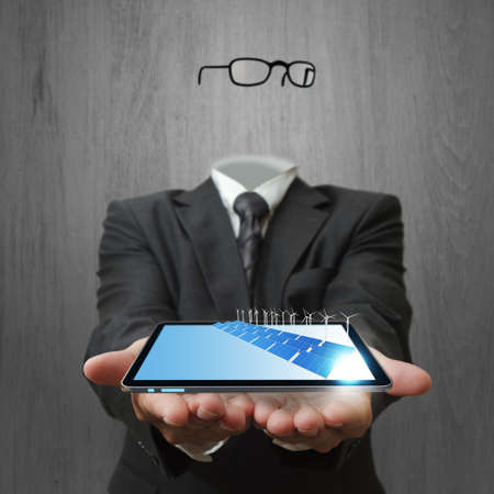 invisible business man hand shows tablet computer and green energy photo