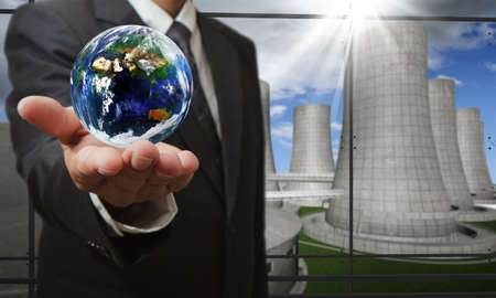 desechos toxicos: la mano del hombre de negocios muestra la tierra y el fondo de las centrales nucleares, elementos de esta imagen proporcionados por la NASA