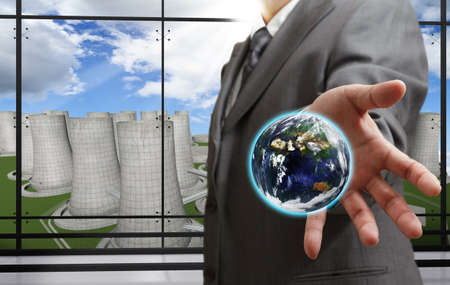 electric power station: business man shows the earth with nuclear power plant background,Elements of this image furnished by NASA Stock Photo