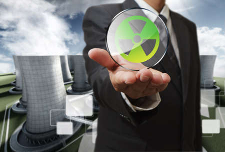 business man hand shows nuclear sign and nuclear power plant background photo