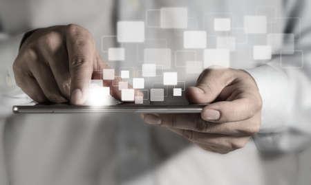usando computadora: Un adulto joven que trabaja en una tableta digital