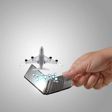 business man hand holds laptop and dream travel photo