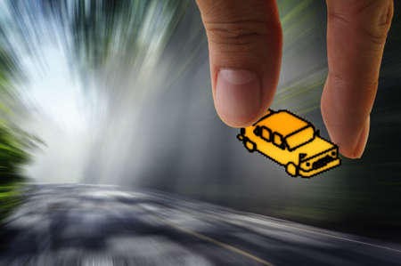 hand picks pixel car icon on the road with motion blur background as concept Stock Photo - 13652490