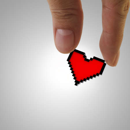 close up of fingers picking up pixel heart icon photo