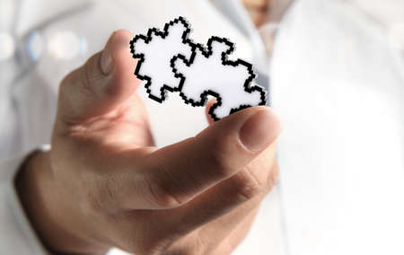 close up of hand picking up pixel puzzles icon as partnership business concept Stock Photo - 13652471