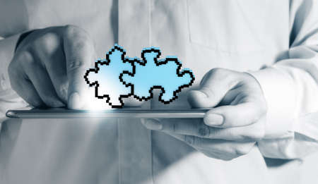 Close up of a man using tablet computer and pixel puzzle as partnership concept Stock Photo - 13652449