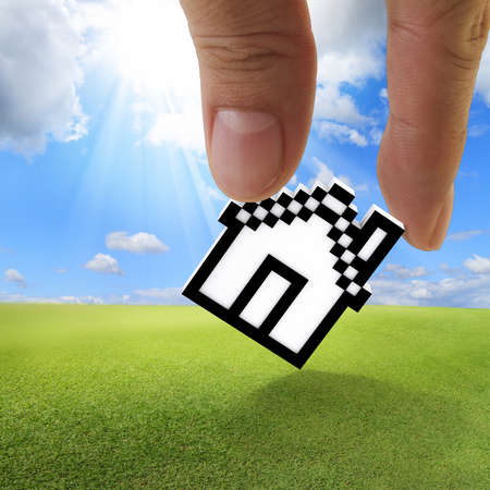 close up of fingers picking up pixel house icon as concept photo