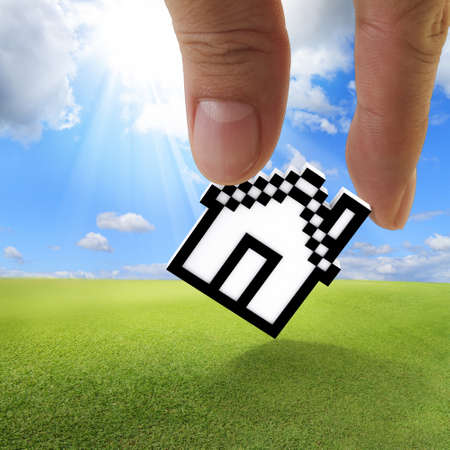 close up of fingers picking up pixel house icon as concept Stock Photo - 13652520