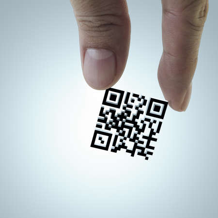 bar code reader: close up of hand picks Qr code as concept Stock Photo